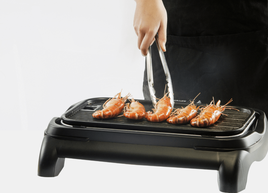 man cooking on an electric griddle