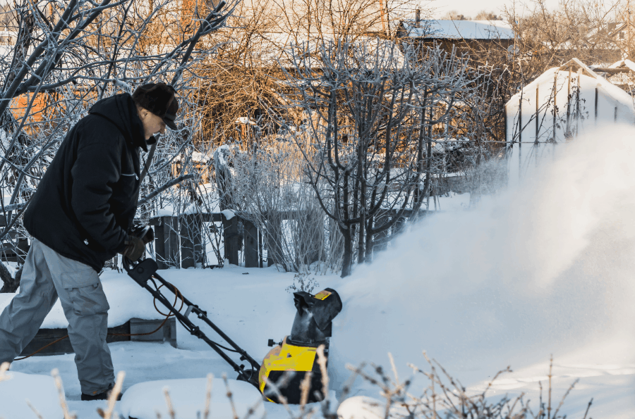 man clearing drive with electric snow blower