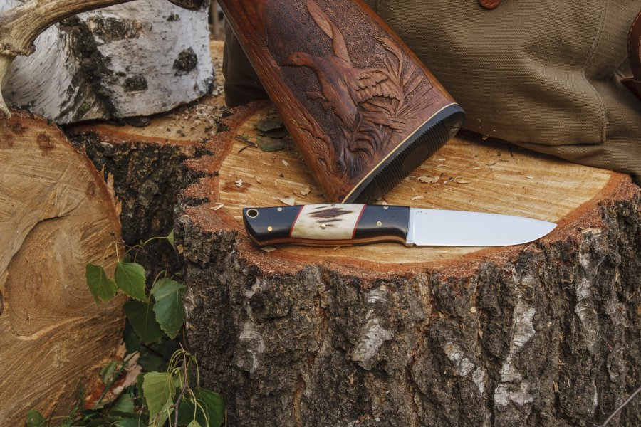 bushcraft knife on a log with a rifle