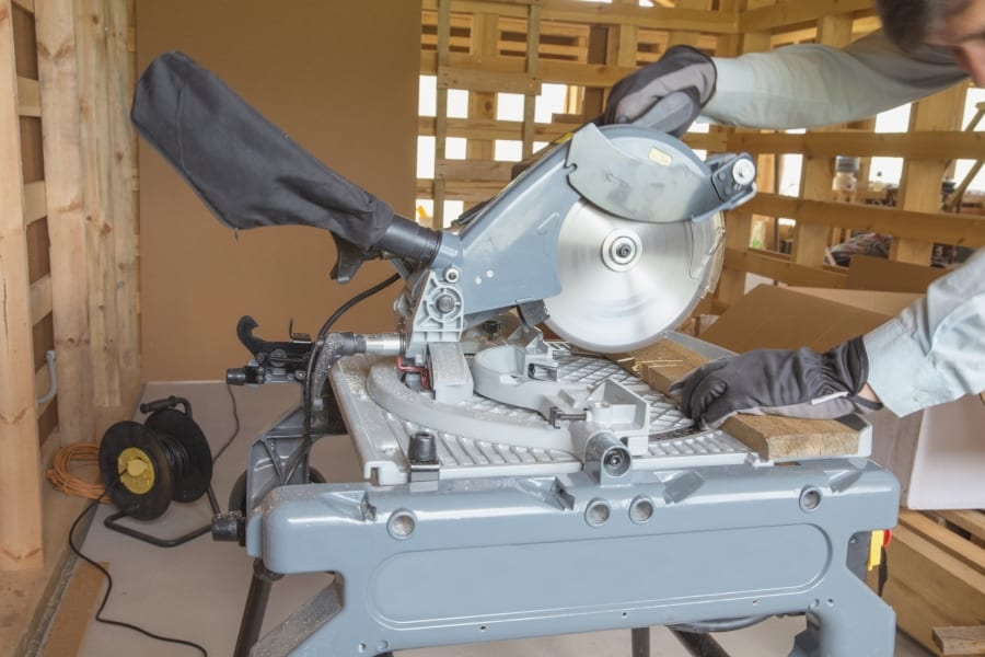 miter saw stand with miter saw cutting wood