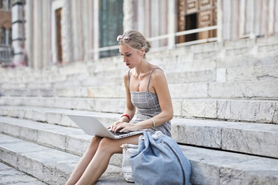 woman using laptop with wifi antenna on steps in front of a building