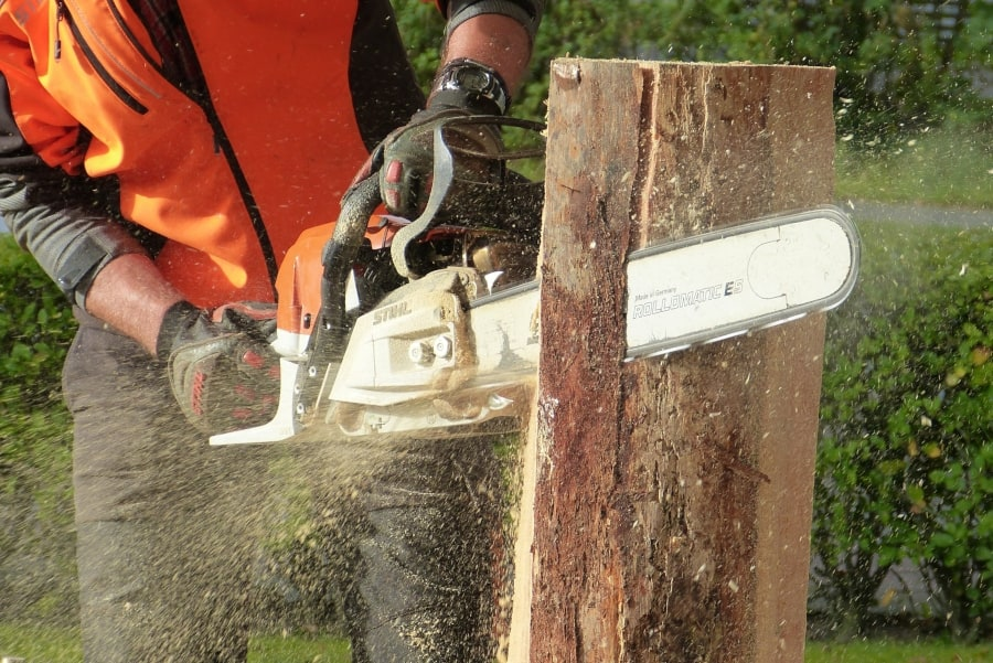 man cutting a stump with a chainsaw equipped with a new chain